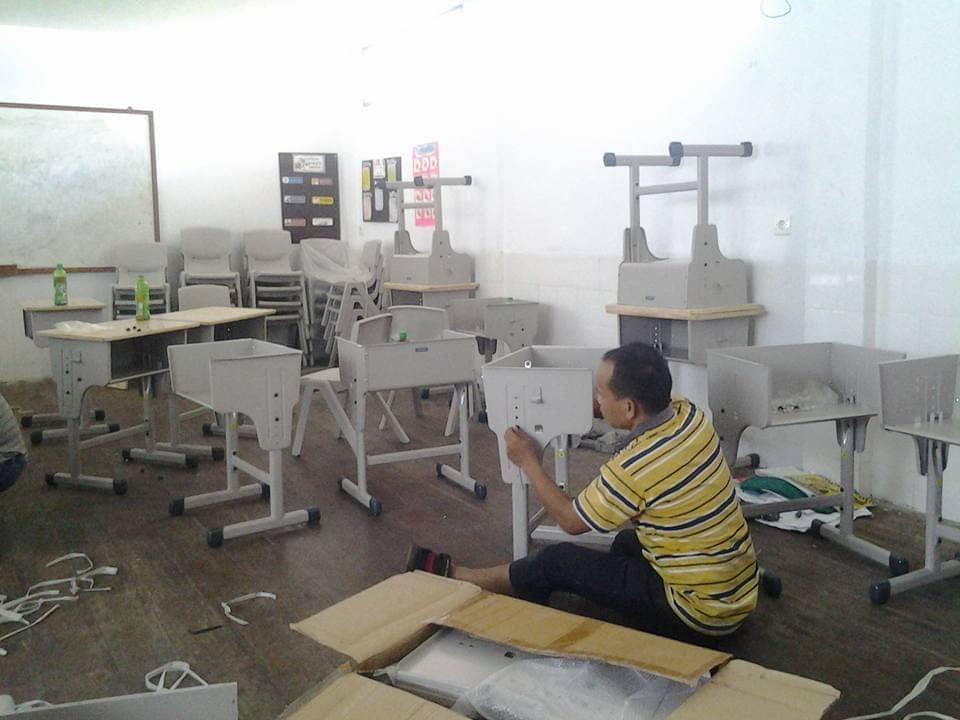 Guru SD, Bpk. Tulus Sihombing, merangkai bangku baru
