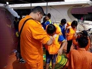 Para siswa belajar dan dibantu memakai baju pelampung